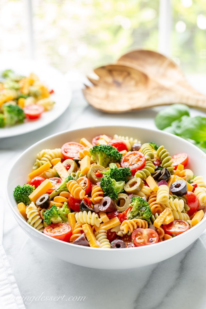 A bowl of easy pasta salad with broccoli, tomatoes and cheese
