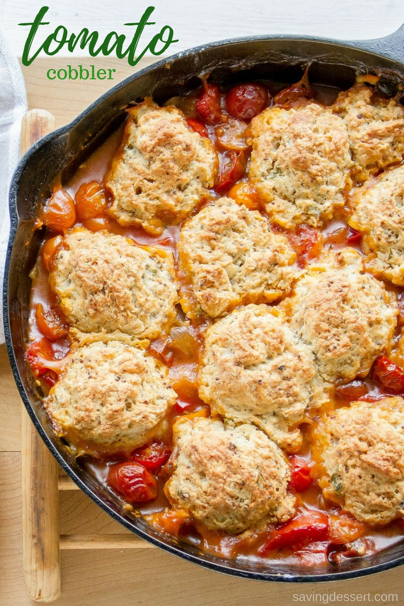 A cast iron skillet filled with fresh tomato cobbler topped with herbed biscuits