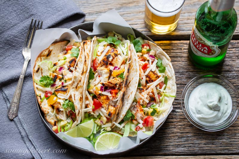 Grilled Fish tacos with cabbage, cheese, limes and corn salsa