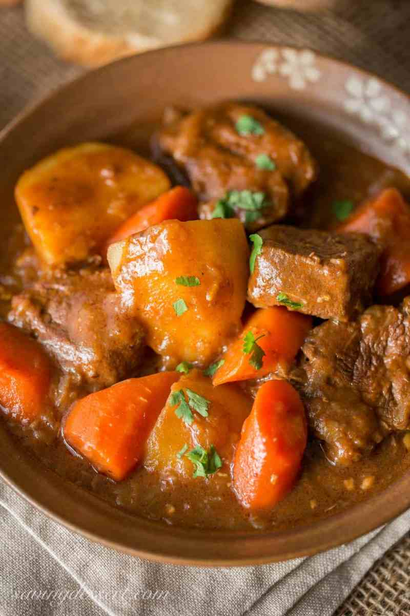 A bowl of Guinness Beef Stew with potatoes, carrots and big chunks of tender beef. Topped with fresh parsley