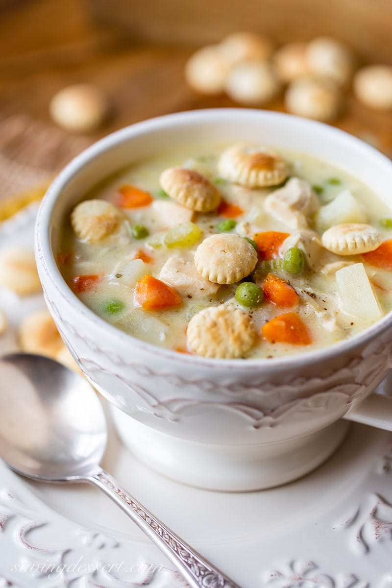 A bowl of chicken pot pie soup with oyster crackers on top