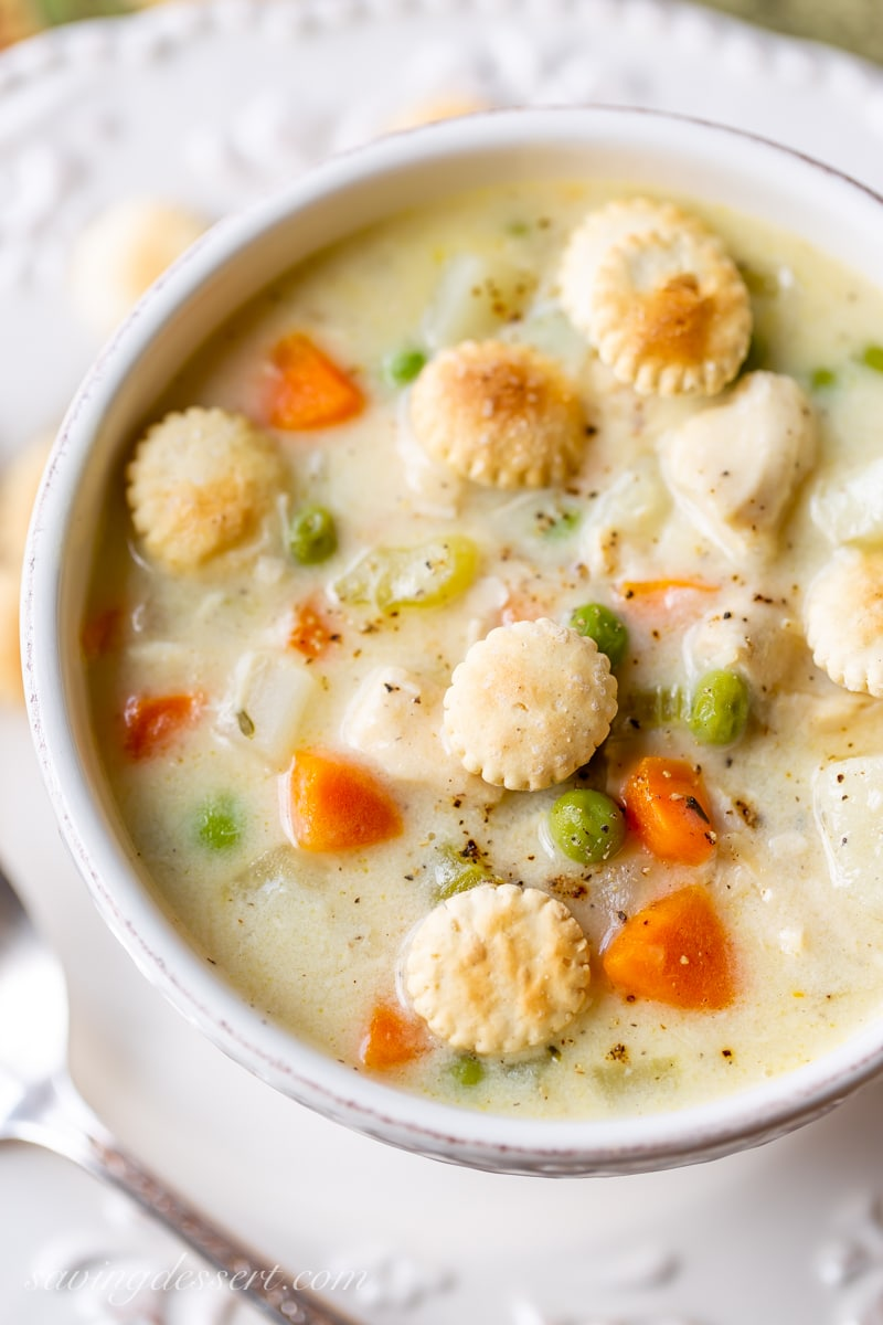 A bowl of chicken pot pie soup with carrots, peas, potatoes and oyster crackers on top
