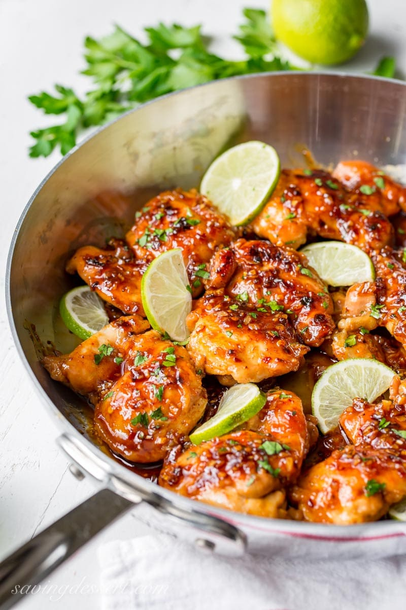 A skillet filled with spicy honey lime chicken thighs with lime wedges
