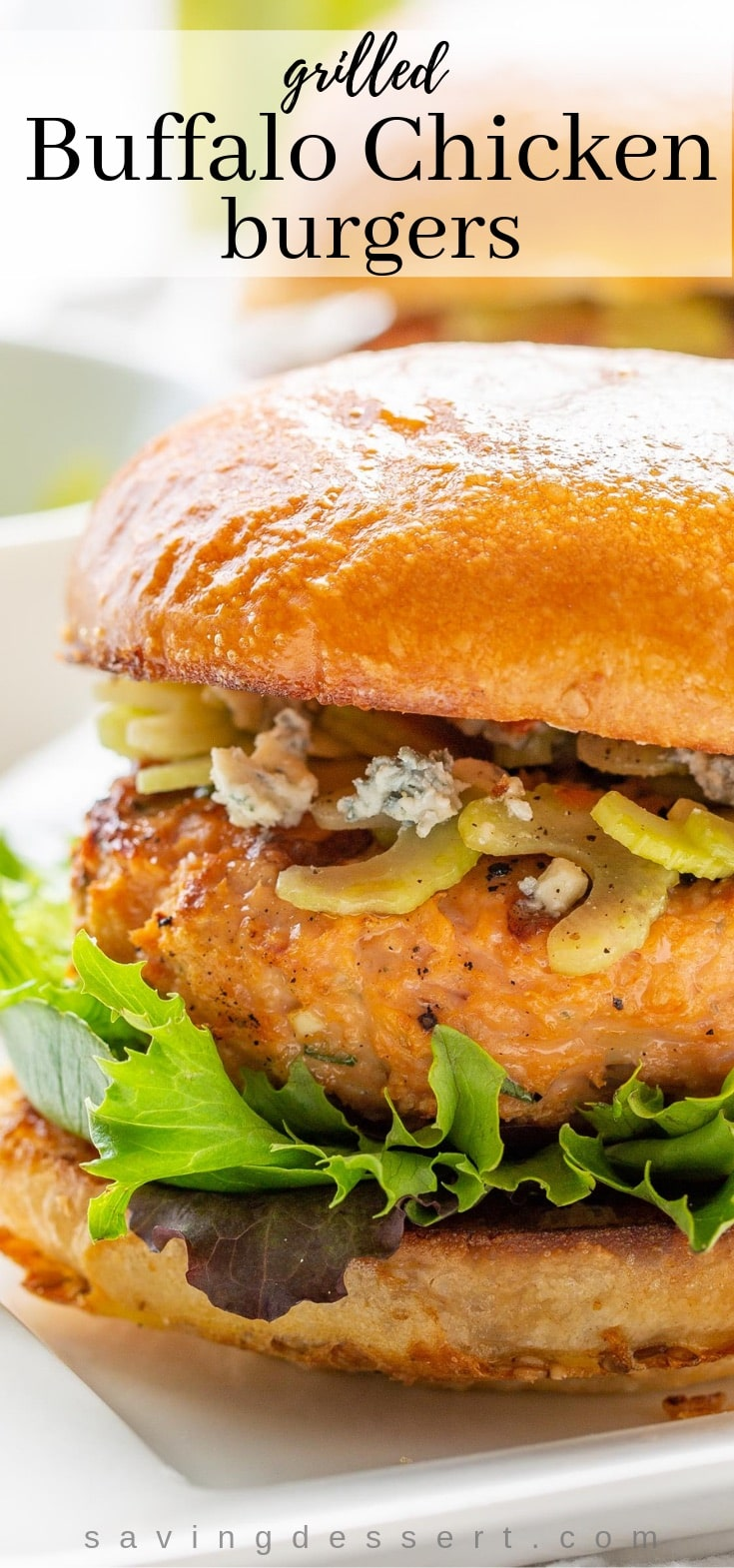 A close up of a grilled Buffalo Chicken burger with blue cheese, lettuce and a celery salad on a toasted bun