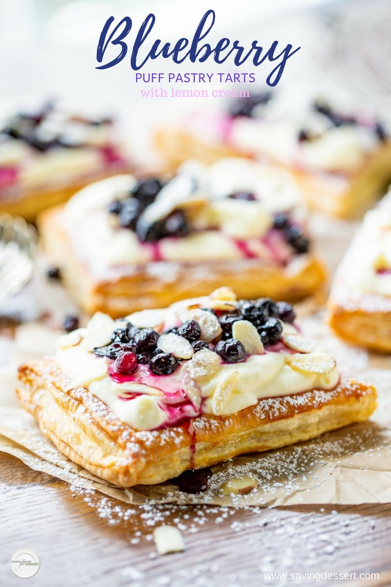 Blueberry puff pastry tarts filled with lemon cream and topped with sliced almonds and a dusting of powdered sugar