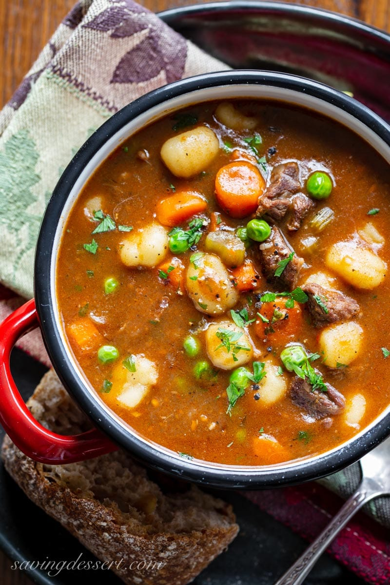 A bowl of Hearty Beef and Gnocchi Soup with carrots, peas and fresh parsley