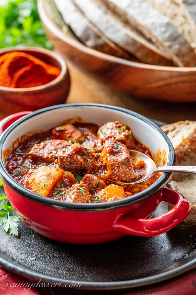 a spoonful of tender beef from a bowl of Hungarian style beef Goulash. Served with bread and topped with fresh chopped parsley