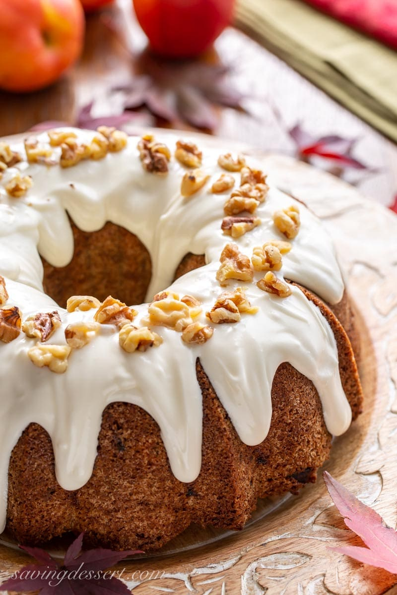 Fresh apple cake topped with a creamy icing and walnuts