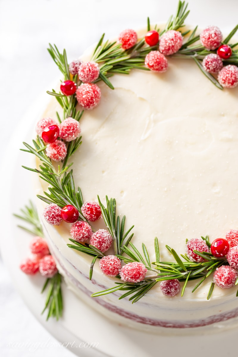 An overhead shot of red velvet cake decorated with rosemary and sugared cranberries