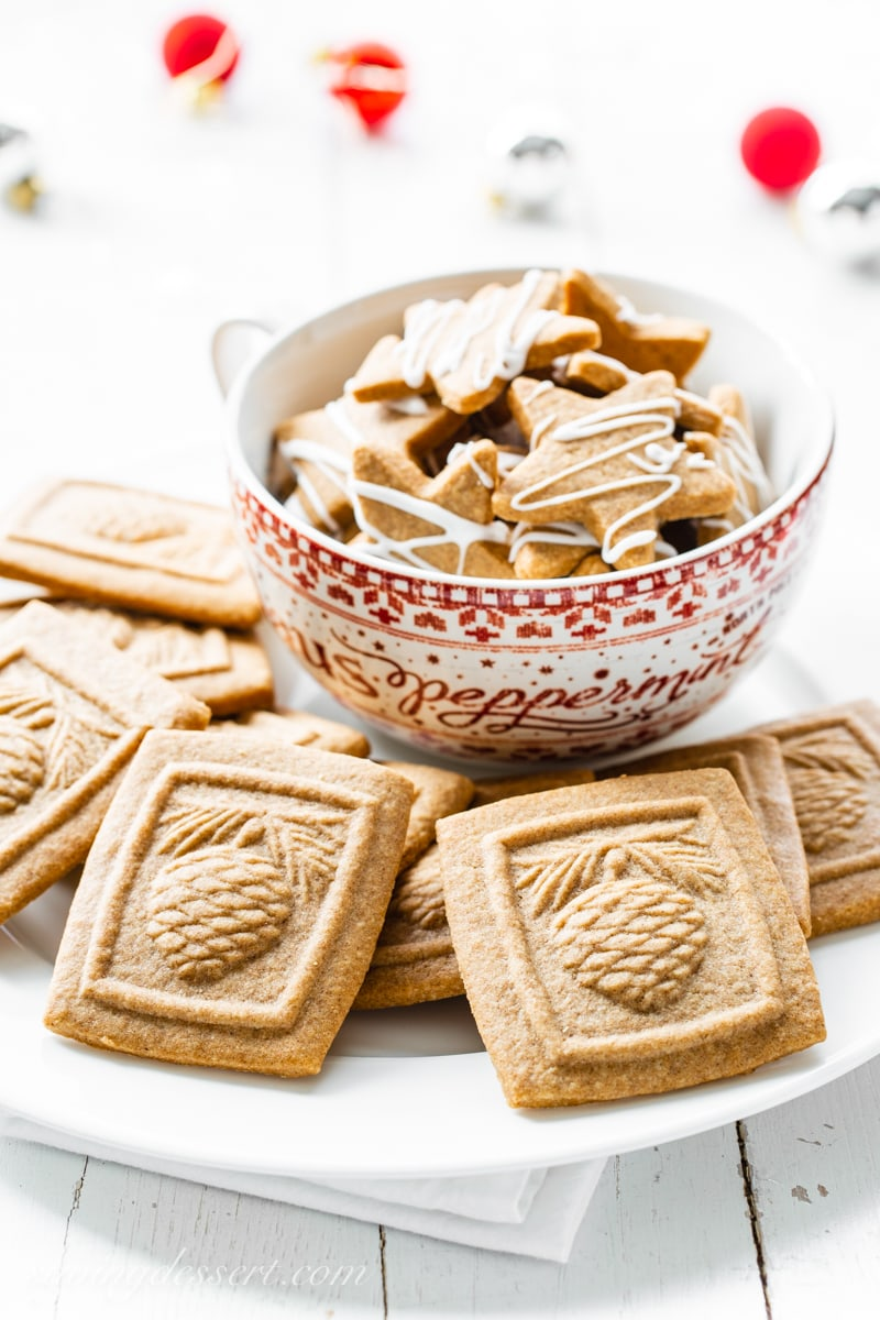 A platter and cup of molded Speculaas Spiced Cookies imprinted with a pine cone design