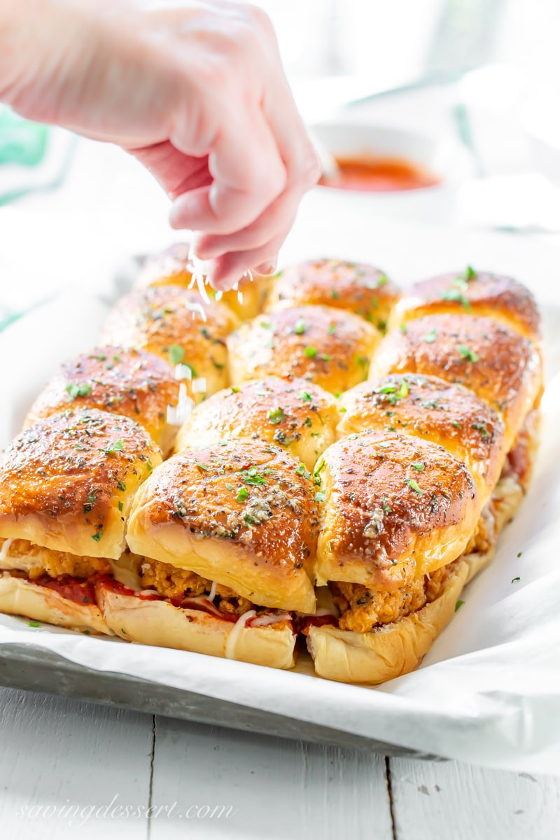A tray of Chicken Parmesan Sliders topped with a garlic herb sauce and sprinkled with fresh parsley and grated Parmesan