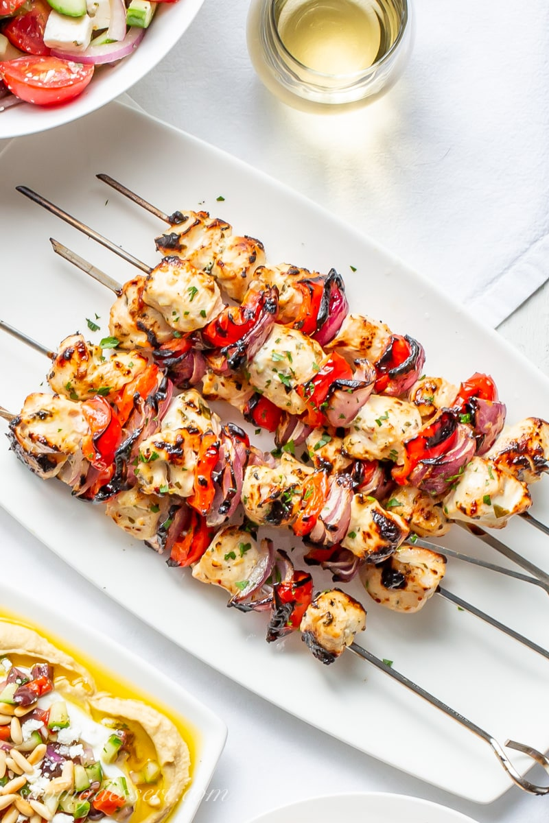 A plate of grilled Greek Chicken skewers with red peppers and purple onions
