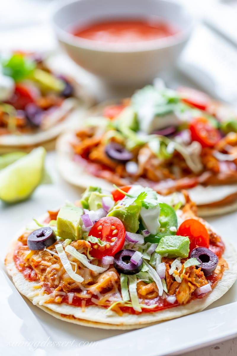 Easy Mexican Pizza with tomatoes, olives, shredded lettuce, spicy chicken and onions