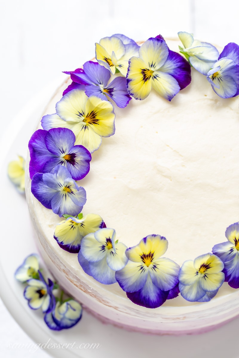 An overhead view of a pretty three layer cake decorated with blue and yellow pansies