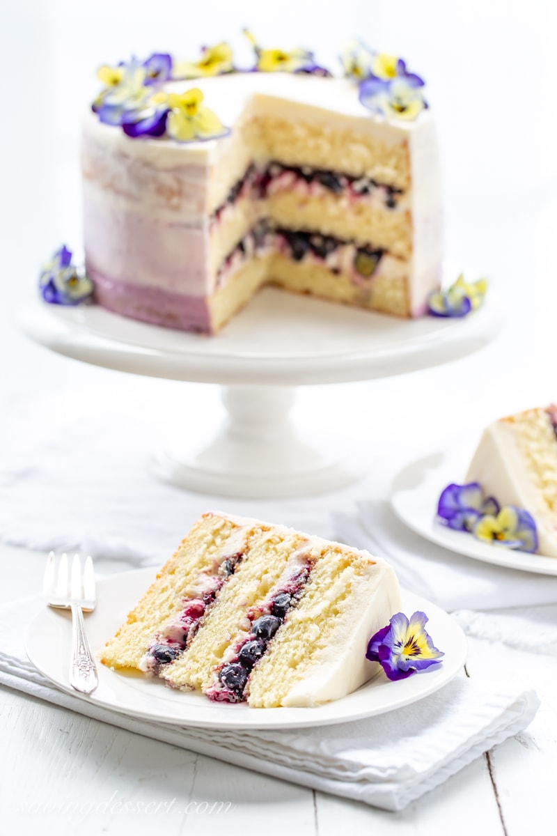 A sliced three layer lemon cake with blueberry filling garnished with blue and yellow pansies