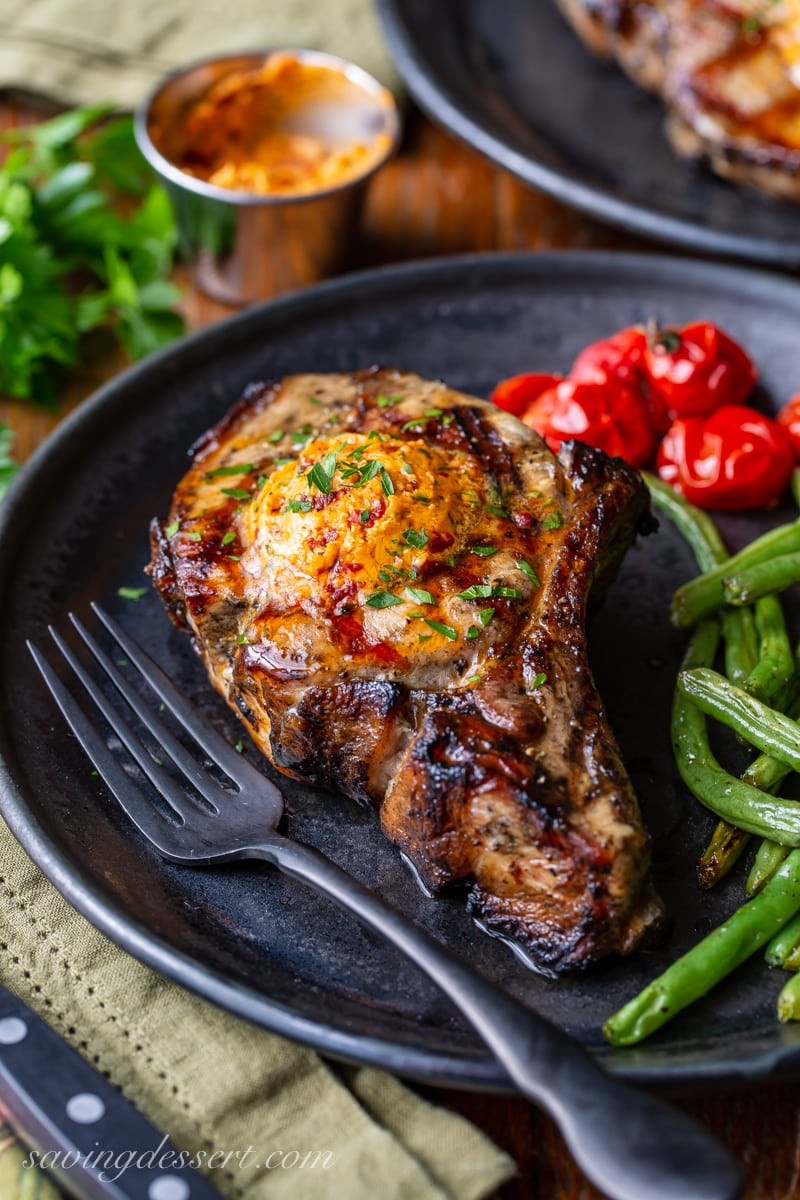 A thick cut grilled pork chop topped with chipotle butter served with green beans and roasted tomatoes