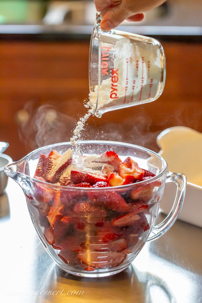 A bowl of strawberries mixed with sugar and cornstarch