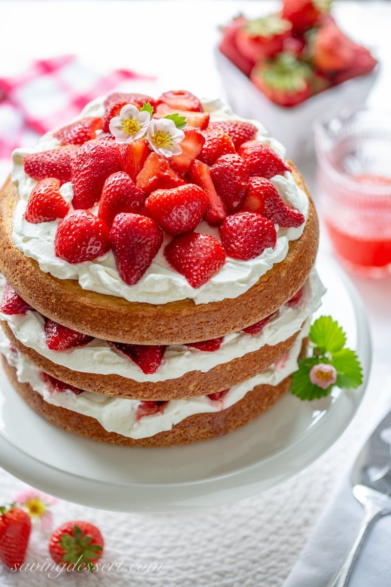 A three layer Strawberry Shortcake Cake filled with whipped cream and topped with red ripe strawberries and a few strawberry blossoms