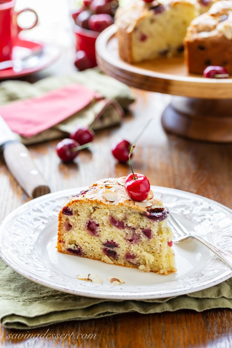 a piece of cherry almond breakfast cake garnished with a fresh red cherry