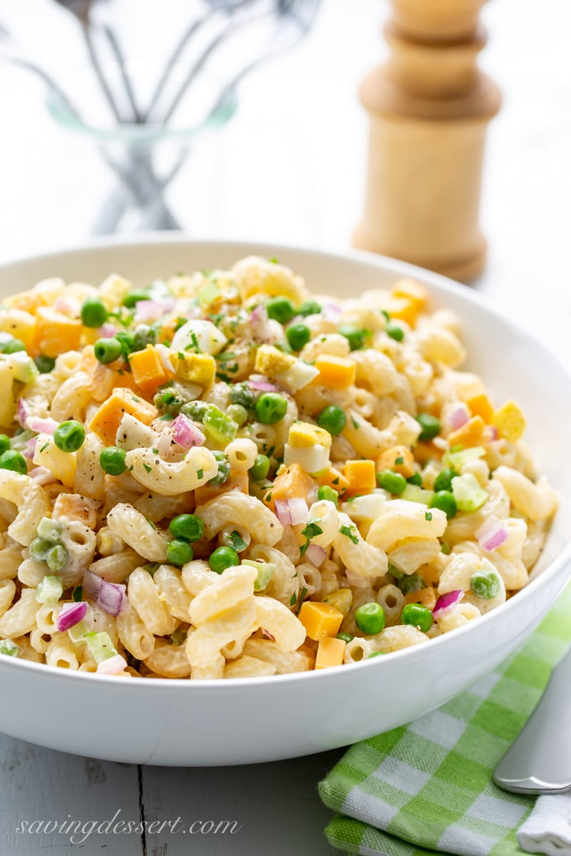 A bowl of macaroni salad with peas, cheese and red onion