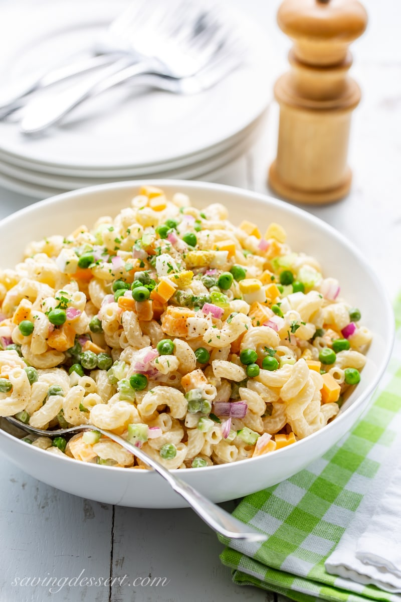 A bowl of macaroni salad with peach, red onion and cheddar cheese chunks