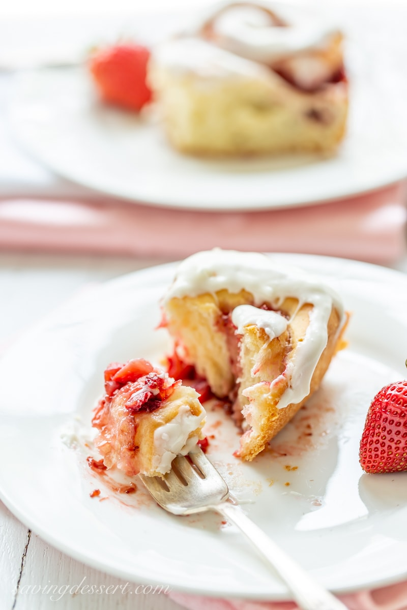 A strawberry sweet roll filled with strawberry jam and fresh berries topped with cream cheese icing