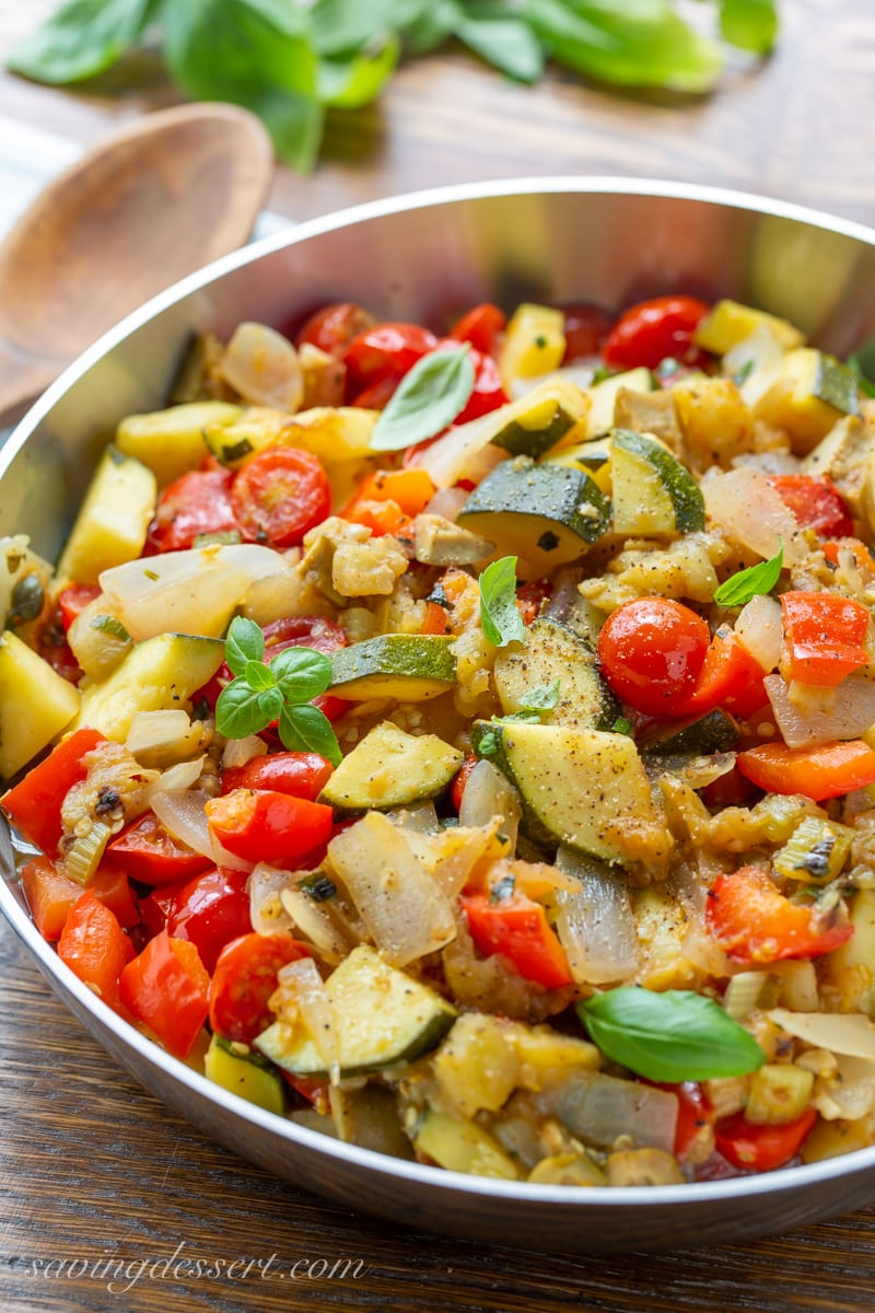 A skillet filled with eggplant caponata with zucchini, onions, tomatoes and fresh basil