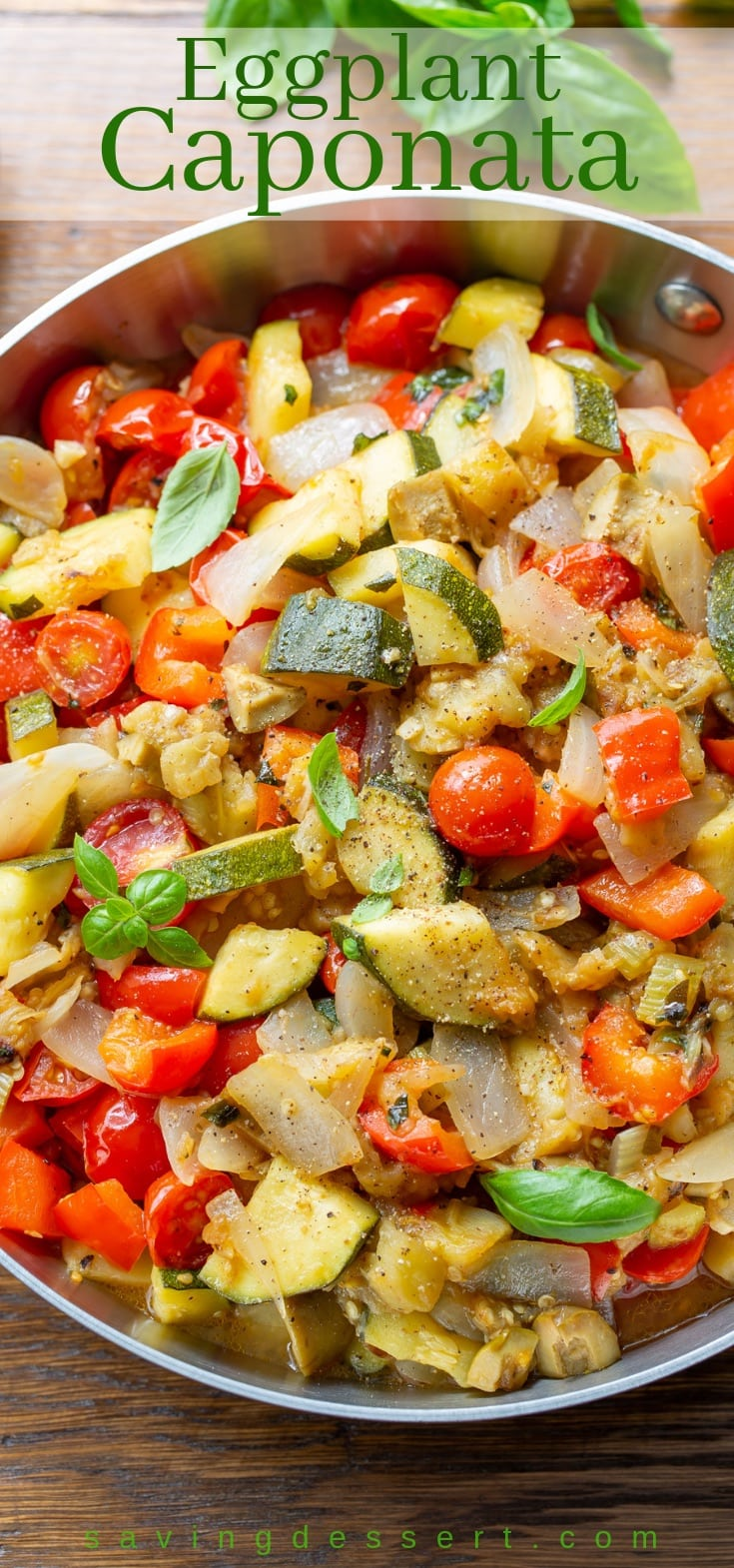 A skillet with eggplant caponata with zucchini, onions, peppers and fresh basil