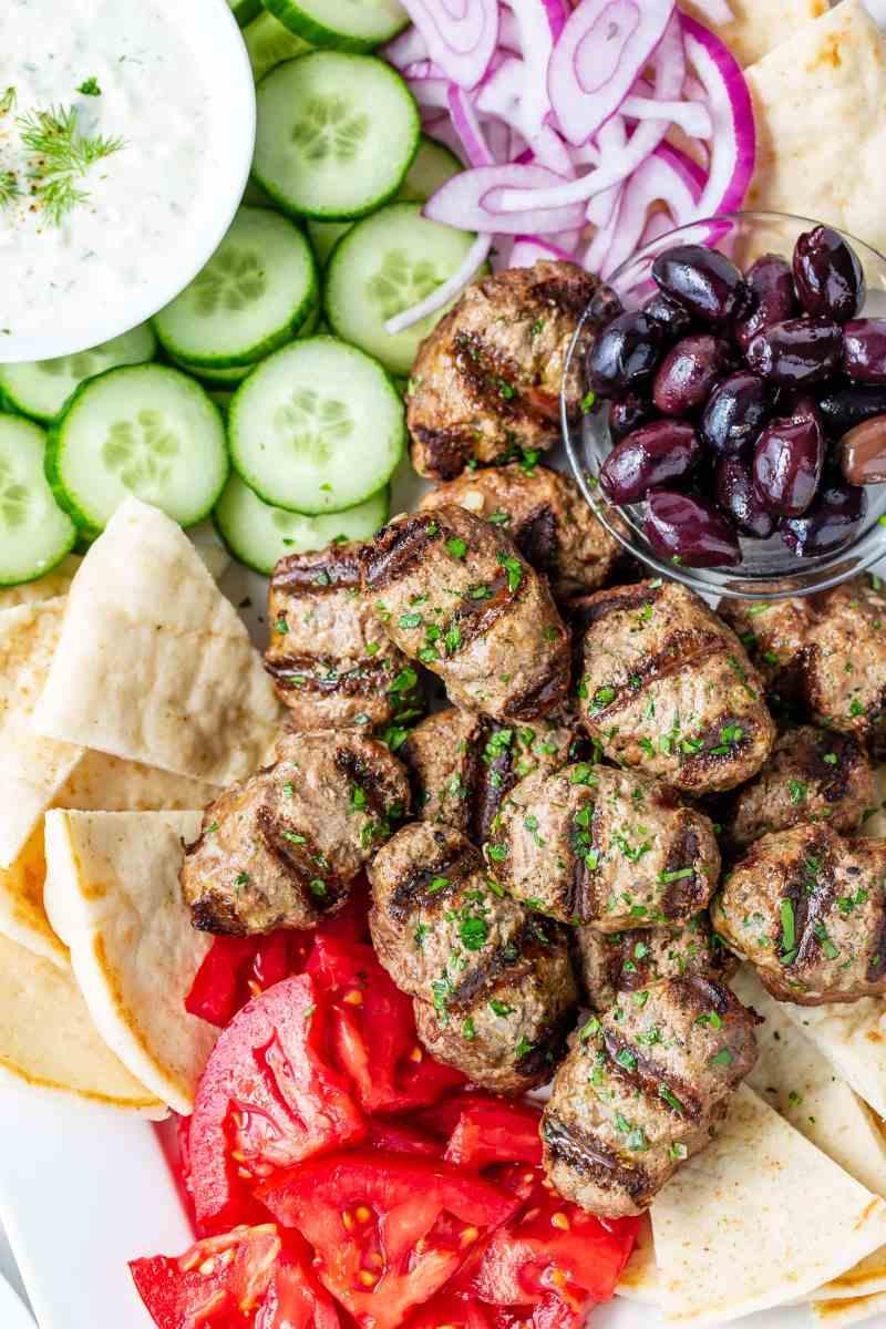 A Greek platter of kebabs, olives, tomato, cucumber-yogurt sauce, onion and pita wedges