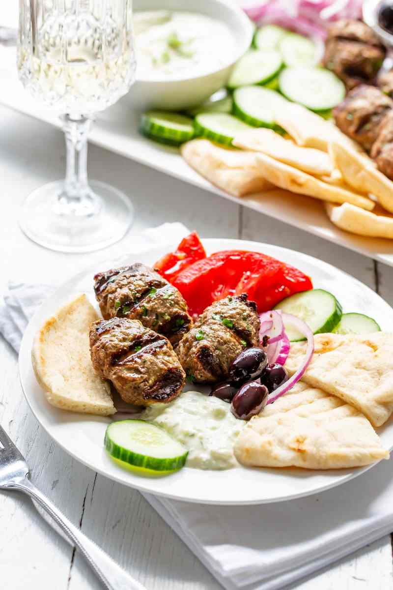 A small plate (meze) with kebabs, cucumber, tomatoes, onion, olives, cucumber-yogurt sauce and pita wedges