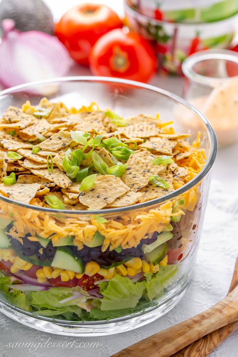 A glass bowl with a layered Mexican Salad with cheese and chips on top