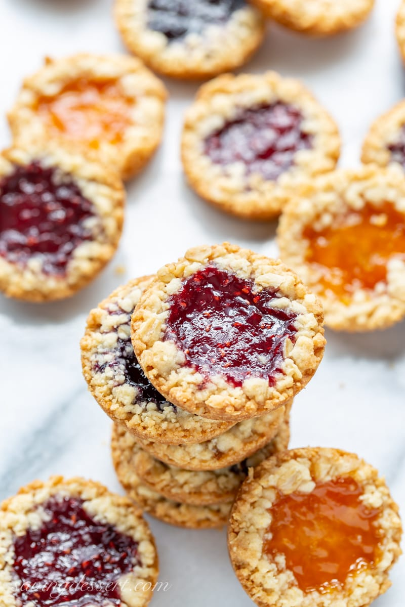 Oatmeal Jammys in a stack with apricot, raspberry and blueberry jam in the middle