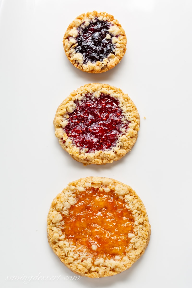 Three Oatmeal Jammy cookies in a line made in different sizes with different jams