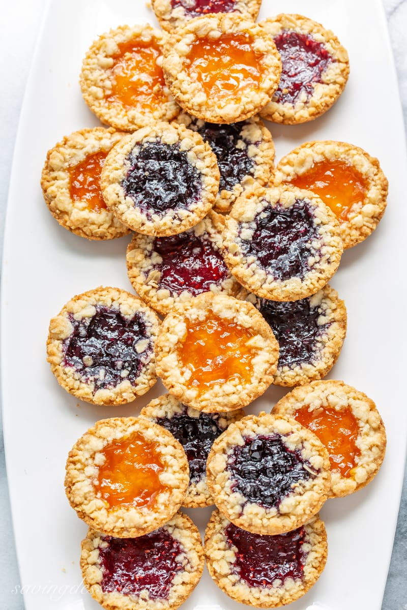 A plate filled with oatmeal jammys with apricot, blueberry and raspberry jam