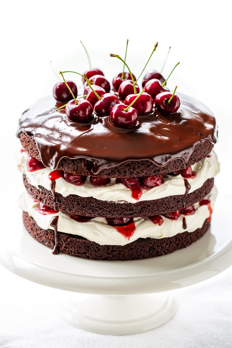 A three layer Black Forest Cake garnished with chocolate ganache and fresh cherries