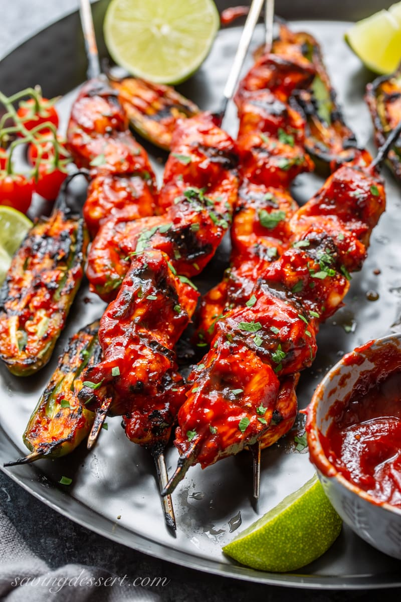 Grilled chicken skewers with charred jalapeño peppers and lime wedges