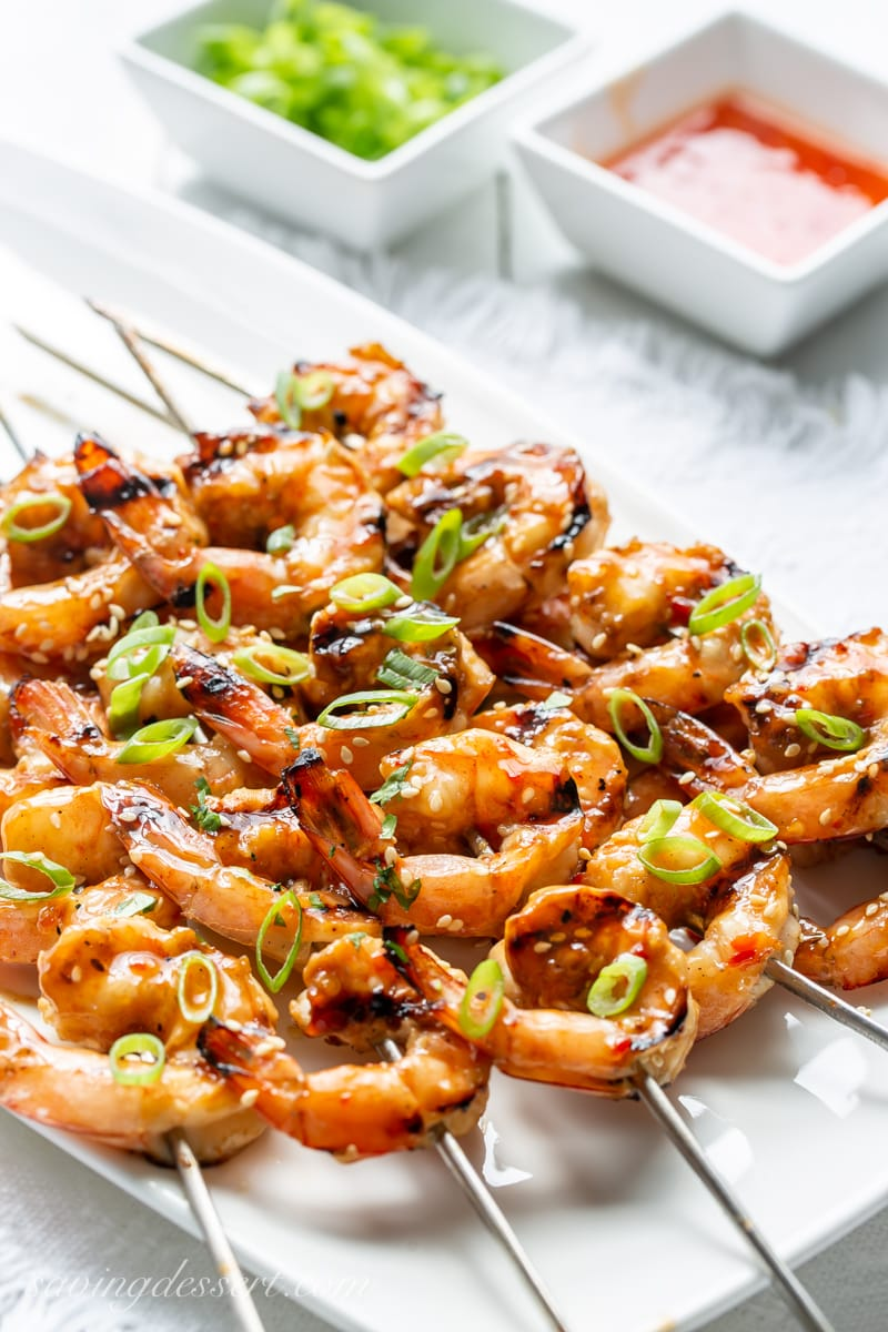 A platter of grilled shrimp skewers topped with sliced green onions.