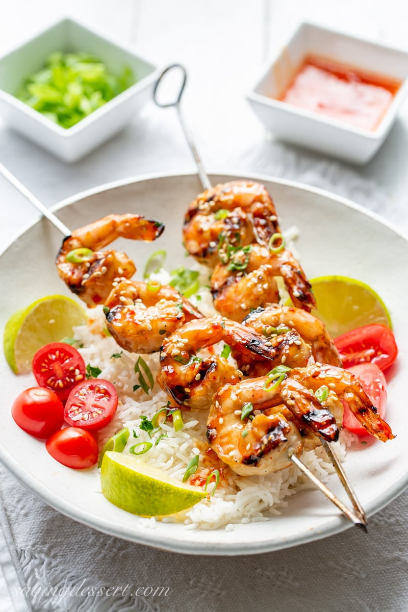 A bowl of rice with lime wedges and sliced tomatoes topped with skewers of Honey Sesame Grilled Shrimp garnished with sliced green onions.