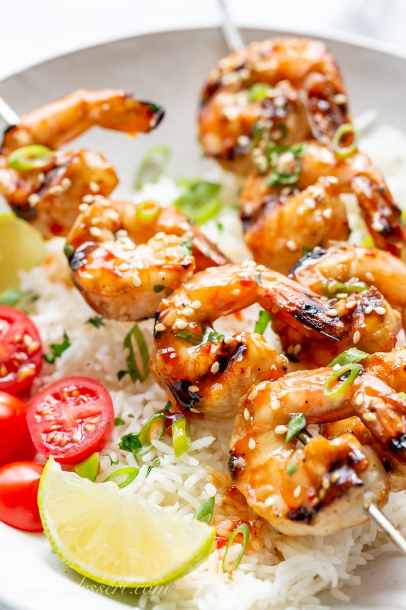 A closeup of grilled shrimp skewers with lime wedges and sliced tomatoes over rice