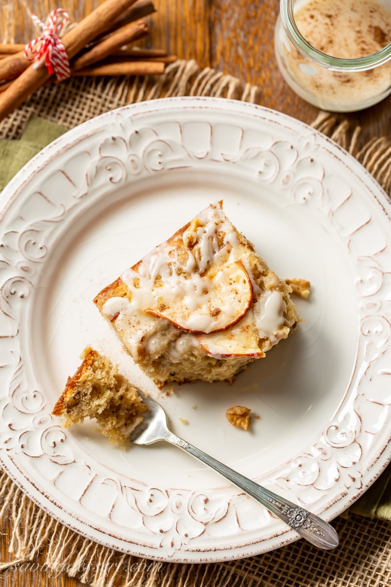 An overhead view of a piece of apple sheet cake with sliced apples on top with a drizzled icing and chopped walnuts
