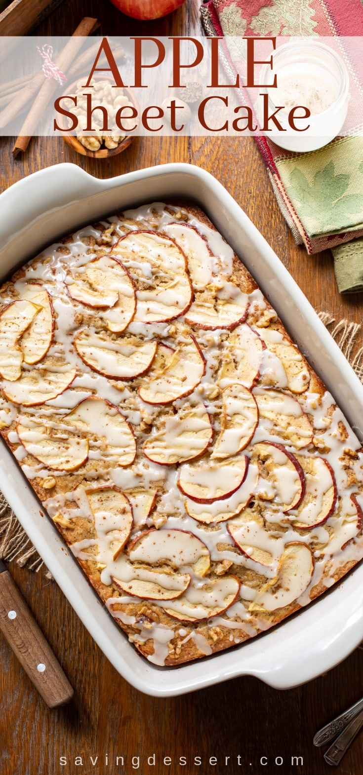 An overhead view of an apple sheet cake topped with sliced apples and walnuts, drizzled with a simple icing and a sprinkle of cinnamon