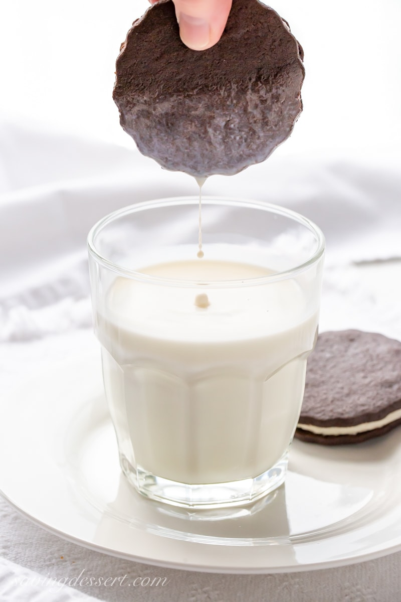 A chocolate sandwich cookie being dipped in a glass of milk - faux Oreos!
