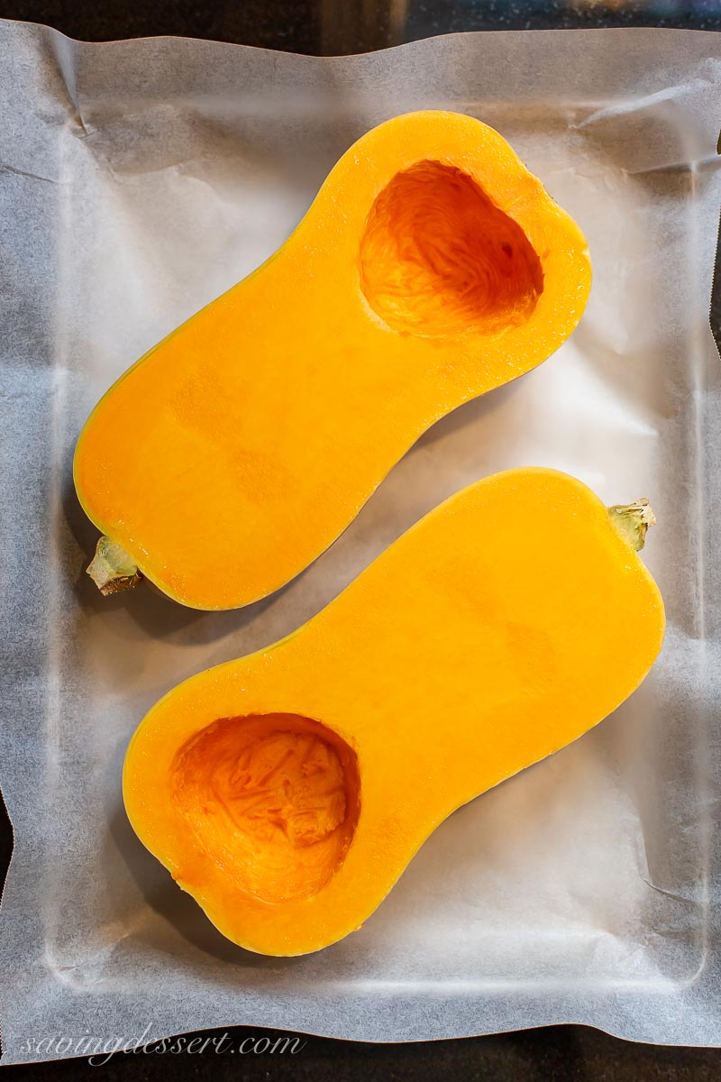 A sliced butternut squash on a baking pan with seeds removed