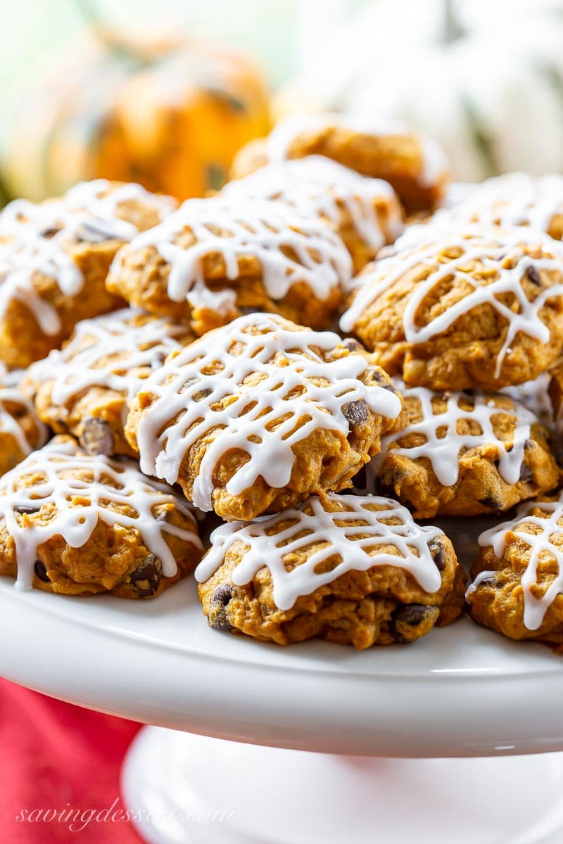 A cake tray piled with pumpkin chocolate chip cookies drizzled with icing