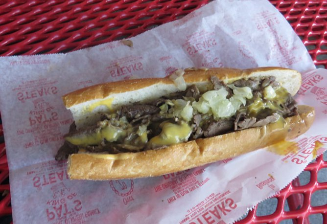 """Pat's signature """"Whiz Wit"""" cheese steak - an Italian bun with sliced rib-eye, grilled onion and Cheese Whiz"""