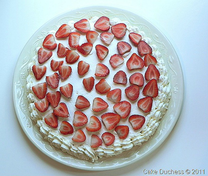 overhead image of cake with strawberries and whipped cream on top