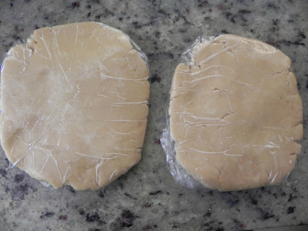 overhead image of pie dough wrapped in plastic wrap