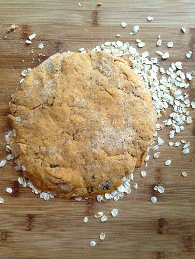 overhead image of dough on wooden surface with oats