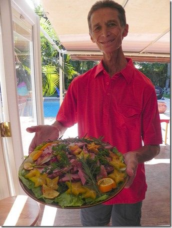 man holding platter of salad
