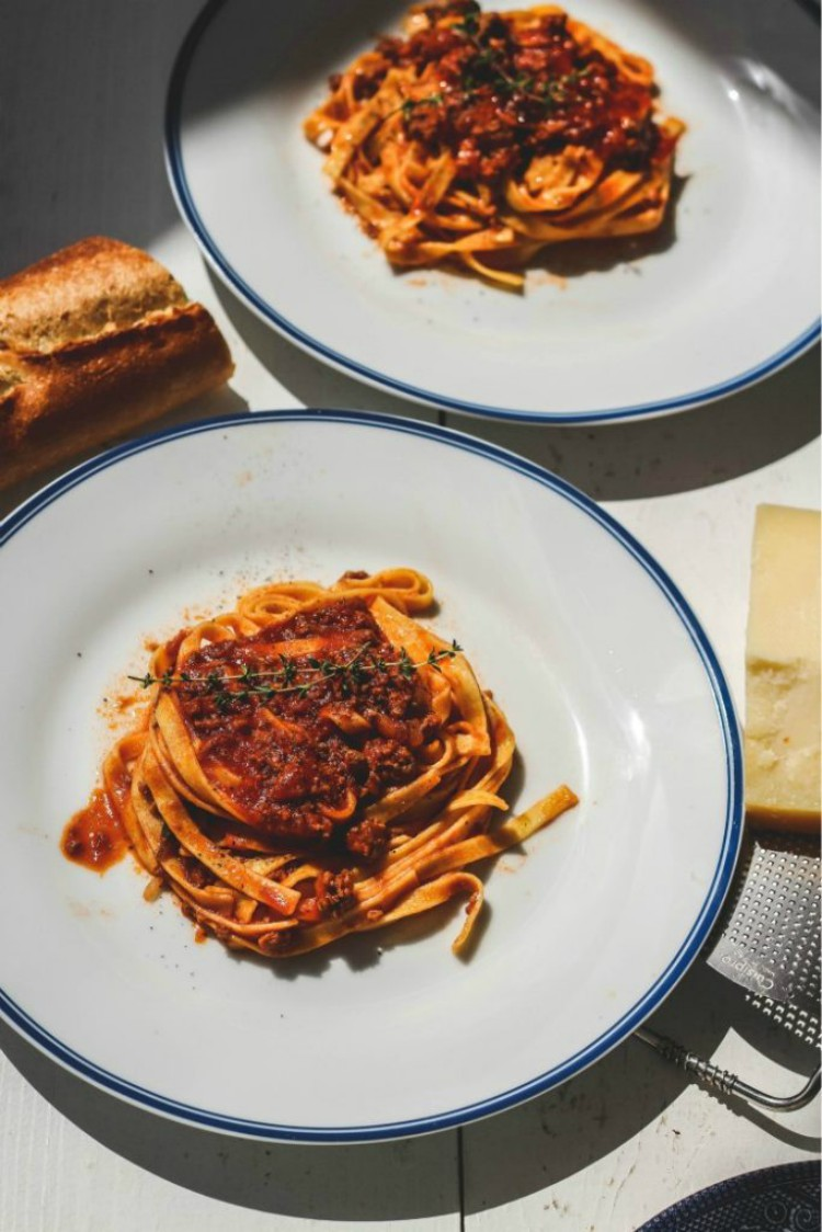 overhead image of pasta with meat sauce and bread on white plates